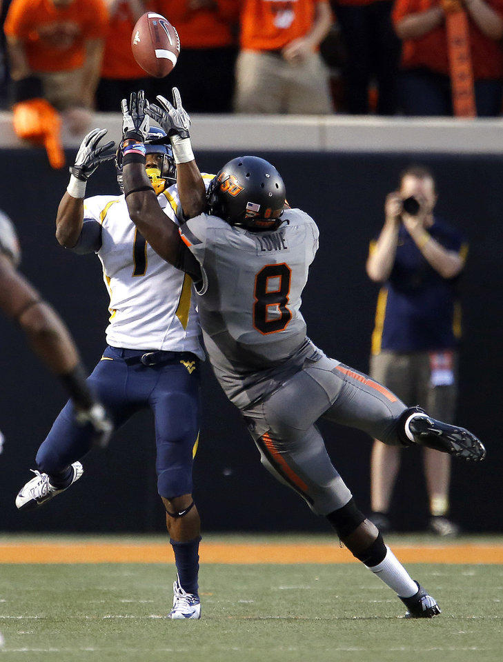 Photo - Oklahoma State's Daytawion Lowe (8) breaks up a pass intended for West Virginia's Tavon Austin (1) during a college football game between Oklahoma State University (OSU) and the West Virginia University at Boone Pickens Stadium in Stillwater, Okla., Saturday, Nov. 10, 2012. Photo by Sarah Phipps, The Oklahoman