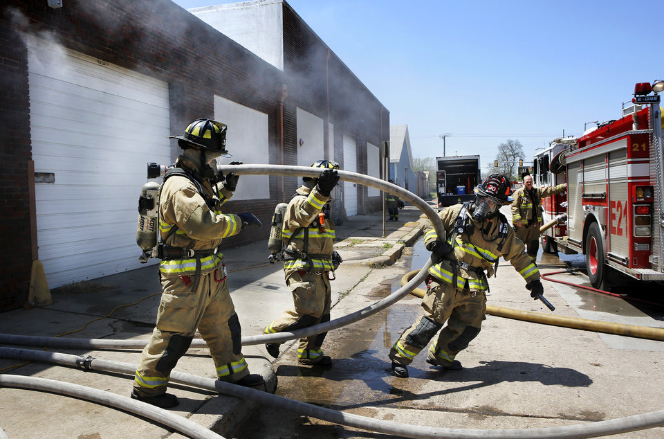 Photo - Smudge pots were lighted and topped with wet hay to fill this vacant building with dense smoke during a recent firefighter training session.Photos by Jim Beckel, THE OKLAHOMANOklahoma City firefighters prepare to enter a smoke-filled vacant building during a training exercise.  Oklahoma City firefighters train in a realistic setting.  Oklahoma City firefighters practice attacking a fire with large hoses during recent training.