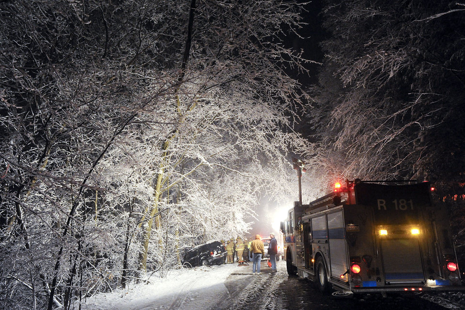 Photo - The driver of a Ford Explorer was uninjured when he lost control of the vehicle on a snow covered Fifth Street Hollow near Bloomsburg, Pa., Friday night, Feb. 8, 2013, and ran off the roadway. Rescue personnel from Espy Fire Company had to secure the SUV which came to rest in the trees at the top of a 30 foot embankment before the driver could climb out. (AP Photo/Bloomsburg Press Enterprise, Jimmy May)