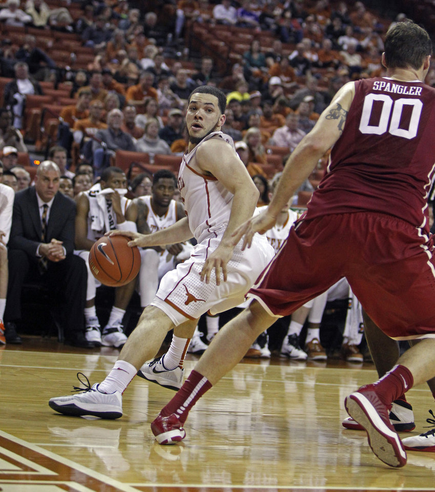 Photo - Texas guard Javan Felix, left, looks to drive around Oklahoma forward Ryan Sprangler, right, during the second half an NCAA college basketball game, Monday, Jan. 5, 2015, in Austin, Texas. Oklahoma won 70-49.  (AP Photo/Michael Thomas)