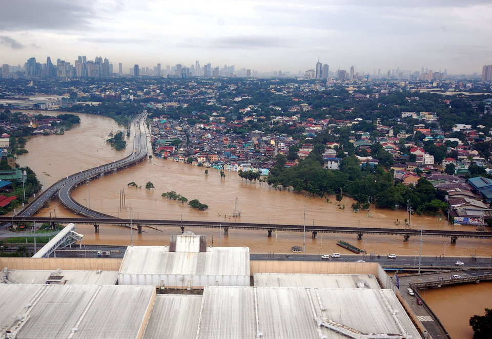 This photo released on Wednesday, Aug. 8, 2012 by the Department of National Defense shows flooded areas in Marikina, east of Manila, Philippines. Widespread flooding battered a million others and paralyzed the Philippine capital began to ease Wednesday as cleanup and rescue efforts focused on a large number of distressed residents, some still marooned on their roofs. (AP Photo/Department of National Defense) ORG XMIT: XAF810