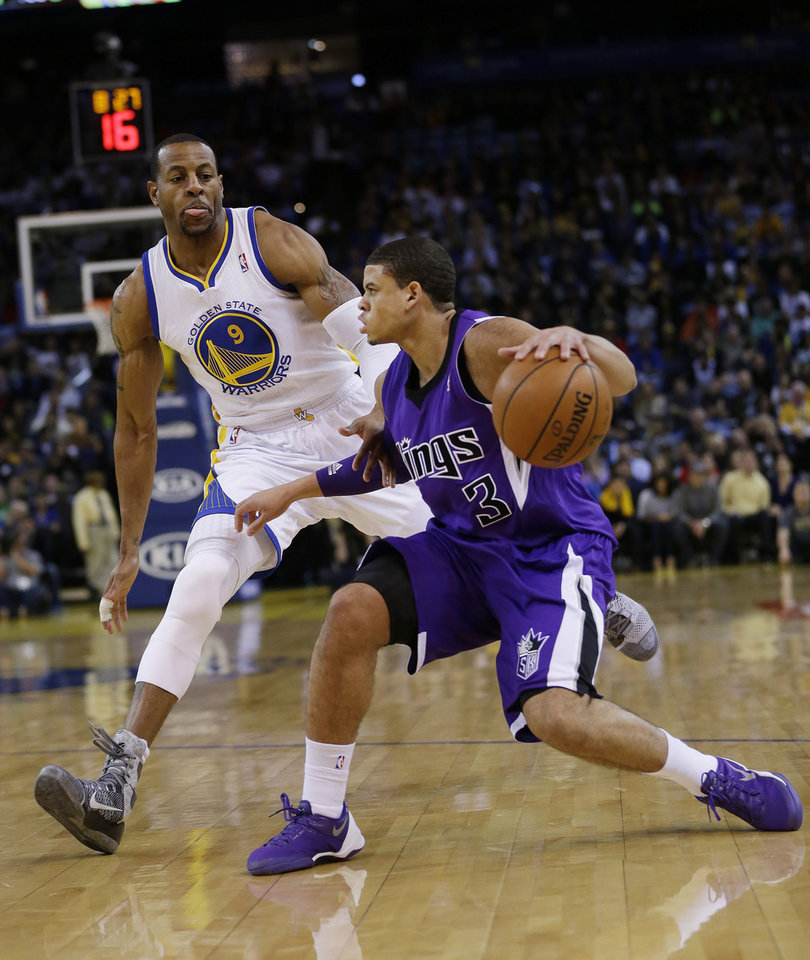 Photo - Sacramento Kings guard Ray McCallum (3) dribbles next to Golden State Warriors forward Andre Iguodala during the first half of an NBA basketball game Friday, April 4, 2014, in Oakland, Calif. (AP Photo/Marcio Jose Sanchez)