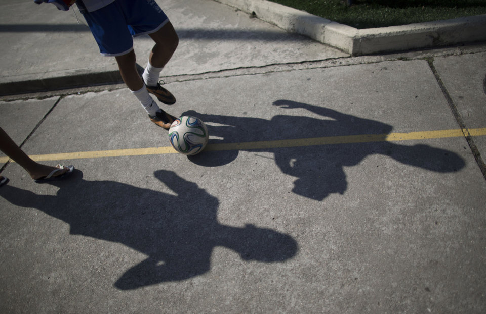 Photo - In this June 17, 2014 photo, Andre Rodrigues de Principe, known as Andrezinho to his neighbors, kicks a soccer ball home after practice in the Vidigal slum of Rio de Janeiro, Brazil. Big league soccer, with its fame and wealth, beckons Andrezinho, even though, at 14, it may already be too late. It's a dream as distant as the stars, but one that still grabs scores of poor Brazilian boys in this soccer-obsessed nation and enchants their families into believing it possible. (AP Photo/Leo Correa)