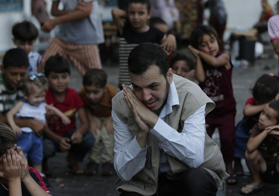 Photo - Volunteer Tarek Zaim, 32, leads a play session with displaced Palestinian children at a U.N. school where they had sought refuge along with their families during the war, in Gaza City, Gaza Strip, Thursday, Aug. 7, 2014. Taking advantage of the continuing ceasefire, volunteers from the local non-profit NGO 'Tomooh' (Ambition), arranged a special play session for children to try and lessen the stress they've been enduring after the weeks of conflict. In the playground the children got a chance to sing and play group games under the caring eye of volunteers. They hope that their efforts will lessen the damage of the traumatic recent weeks events, or at least help them forget for a short while. (AP Photo/Lefteris Pitarakis)