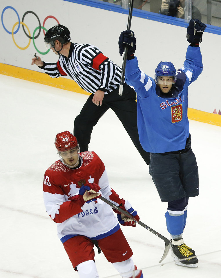 Photo - Finland forward Juhamatti Aaltonen, right, and Russia forward Valeri Nichushkin react after Finland scored a goal in the first period of a men's quarterfinal ice hockey game at the 2014 Winter Olympics, Wednesday, Feb. 19, 2014, in Sochi, Russia. (AP Photo/Mark Humphrey)