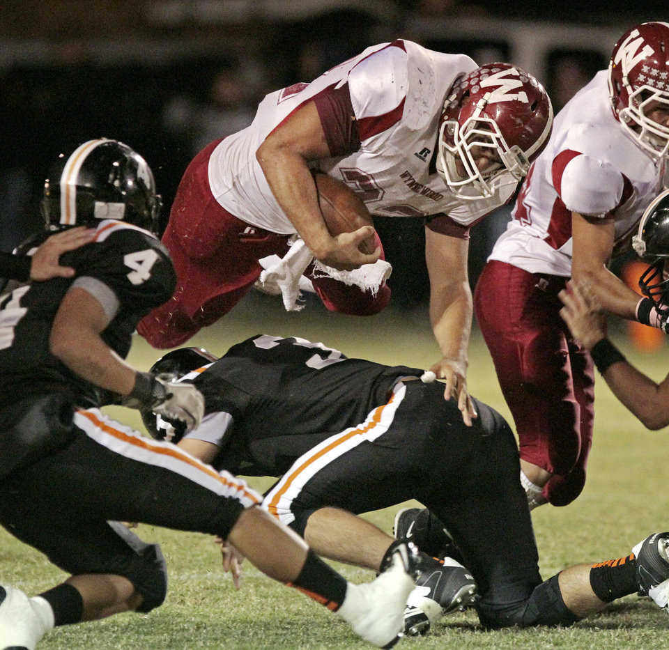 Photo - Wynnewood's Trey Knowles (32) leaps over defensive linemen as the Wayne Bulldogs play the Wynnewood Savages in district 5 class A high school football on Friday, Oct. 28, 2011, in Wayne, Okla.    Photo by Steve Sisney, The Oklahoman ORG XMIT: KOD