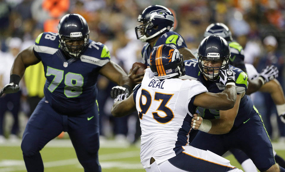 Photo - Seattle Seahawks tackle Mike Person, right, blocks Denver Broncos defensive end Jeremy Beal (93) as Seahawks' Alvin Bailey (78) looks on in the second half of a preseason NFL football game, Saturday, Aug. 17, 2013, in Seattle. (AP Photo/Elaine Thompson)