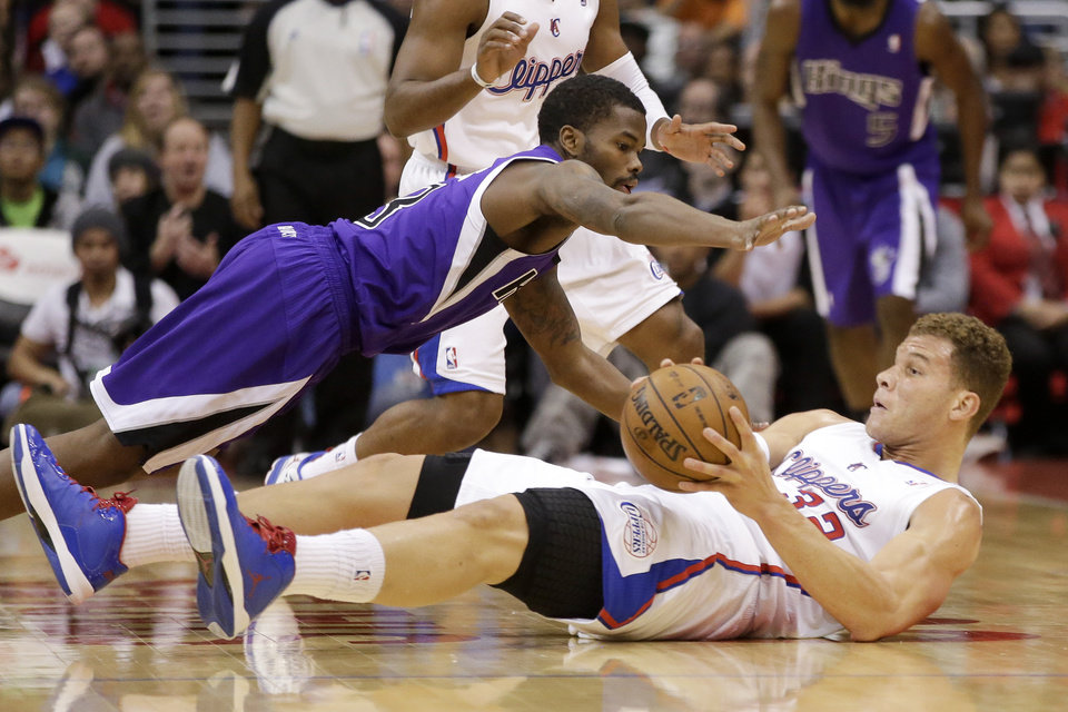 Sacramento Kings' Aaron Brooks, top, and Los Angeles Clippers' Blake Griffin dive for a loose ball during the first half of an NBA basketball game in Los Angeles, Friday, Dec. 21, 2012. (AP Photo/Chris Carlson)