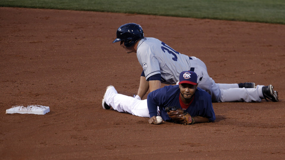 Photo - Oklahoma City's Gregorio Petit (13) and New Orlean's Brian Bogusevic collide at second during the Oklahoma City Redhawks game agains the New Orleans Zephyrs at the Chickasaw Bricktown Ball Park. Friday, April 11, 2014. Photo by Sarah Phipps, The Oklahoman