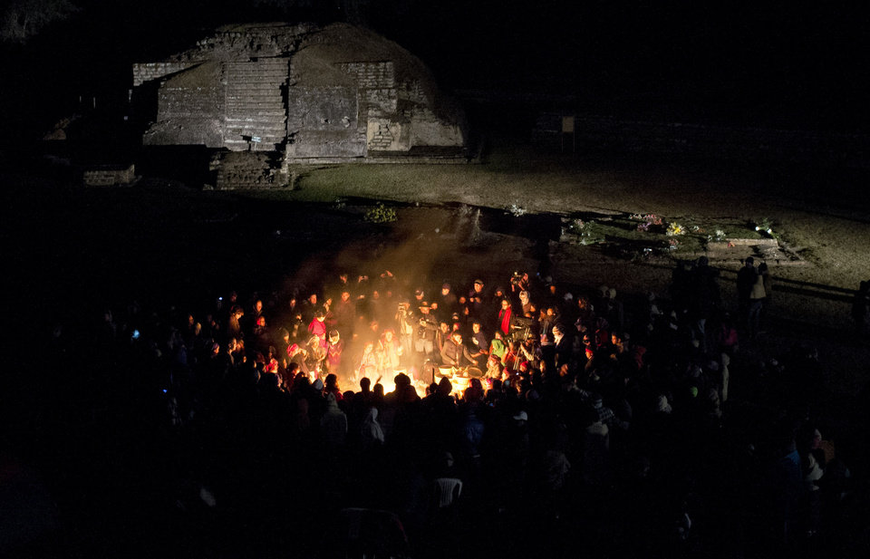 People gather around a sacred fire at the Mayan archeological site of Iximche during a ceremony marking the end of the 13th Oxlajuj B\'aktun in Tecpan, Guatemala, early Friday, Dec. 21, 2012. The end of the 13th Oxlajuj B\'aktun marks a new period in the Mayan calendar, an event only comparable in recent times with the new millennium in 2000. While the Mayan calendar cycle has prompted a wave of doomsday speculation across the globe, few in the Mayan heartland believe the world will end on Friday. (AP Photo/Moises Castillo)