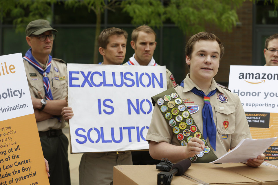 Photo - Pascal Tessier, 17, a gay Eagle Scout from Kensington, Md., right, speaks in front of a group of Boy Scouts and scout leaders, Wednesday, May 21, 2014, outside the headquarters of Amazon.com in Seattle. The group delivered a petition to Amazon that was started as an online effort by Tessier and gathered more than 125,000 signatures, urging Amazon to stop donating money to the Boy Scouts due to the organization's policy of excluding openly gay adults from leadership positions, despite recently accepting gay youth as scouts. (AP Photo/Ted S. Warren)