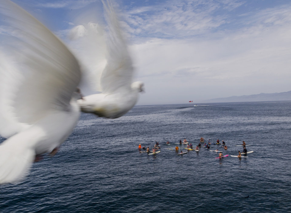 Photo - Doves fly away over a memorial paddle-out for Joe Larson, the original owner of Hinano, as the US Coast Guard holds training exercises at Venice Beach in Los Angeles Monday, July 28, 2014. Los Angeles' popular Venice Beach teemed with people enjoying a weekend outing on the boardwalk and sand when lifeguards and other witnesses say lightning from a rare summer thunderstorm hit without warning, injuring or rattling more than a dozen people and leaving a 21-year-old man dead. The witnesses said the strike hit with a tremendous boom about 2:30 p.m. Sunday, rattling buildings and showering a lifeguard headquarters with sparks. (AP Photo/Damian Dovarganes)