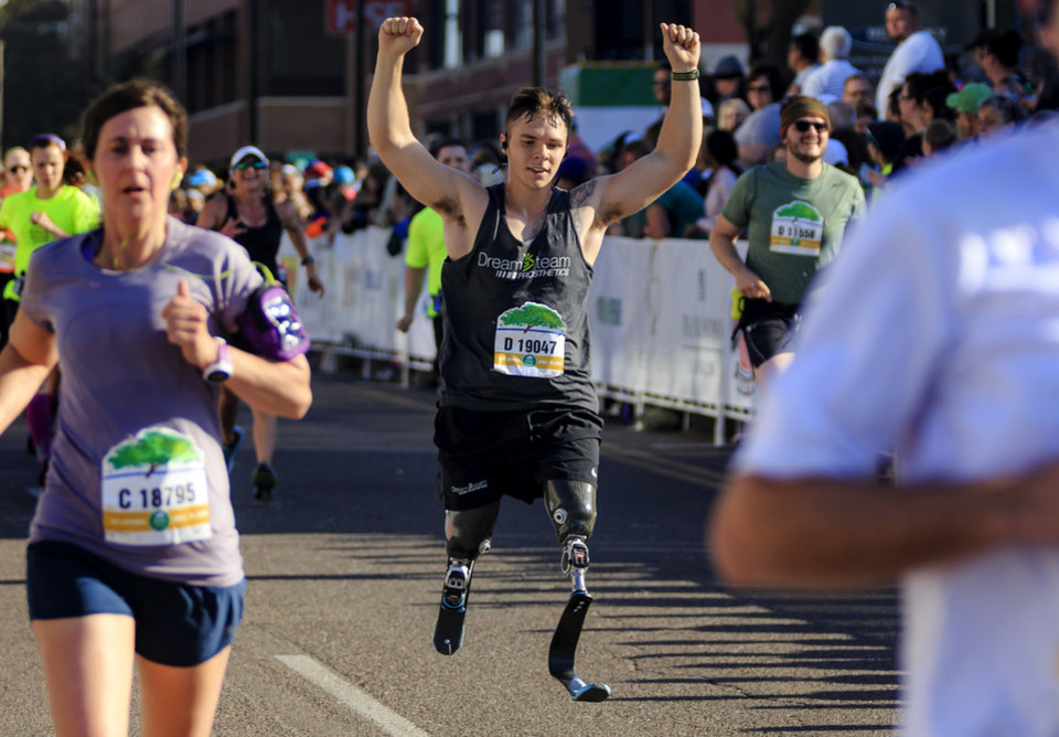 Photo - Seth Alexander celebrates as he crosses the finish line to complete the half marathon during the Oklahoma City Marathon in Oklahoma City, Okla. on Sunday, April 29, 2018.  . Photo by Chris Landsberger, The Oklahoman