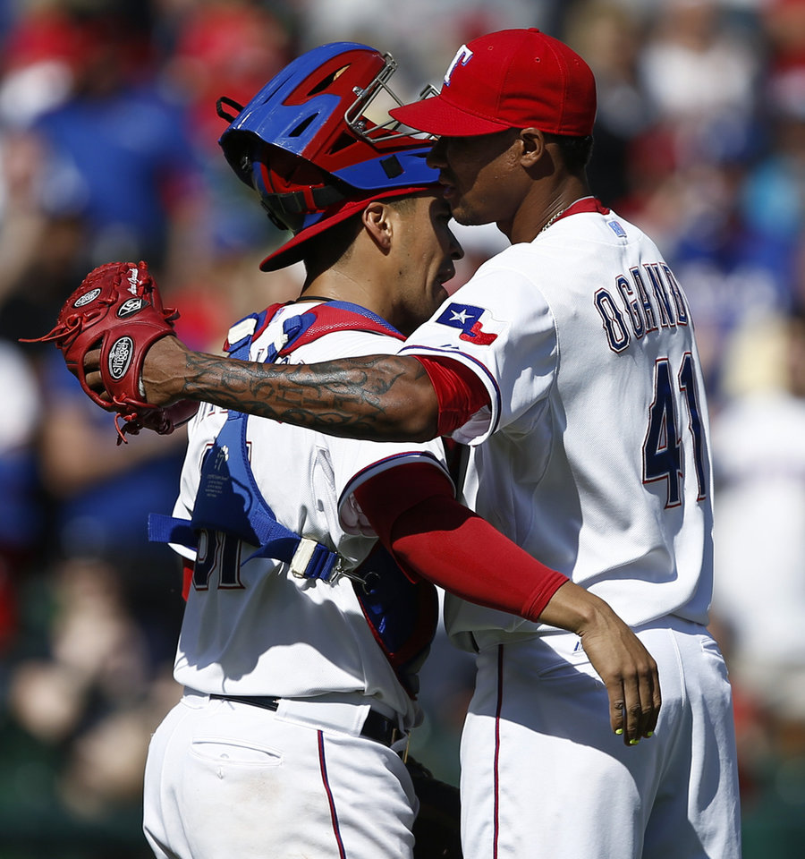 Photo - Texas Rangers starting pitcher Alexi Ogando (41) and catcher Robinson Chirinos (61) congratulate each other after the Rangers' 1-0 win against the Houston Astros in a baseball game, Sunday, April 13, 2014, in Arlington, Texas. (AP Photo/Jim Cowsert)