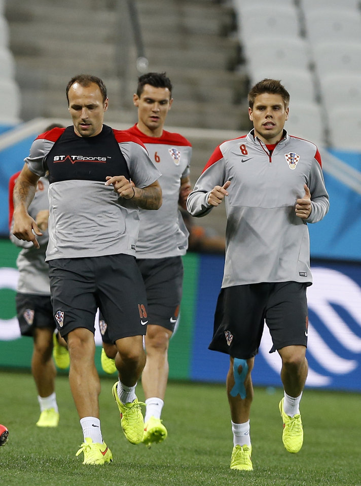 Photo - Croatia's Gordon Schildenfeld, left, Ivica Olic, right and Dejan Lovren run during an official training session the day before the group A World Cup soccer match between Brazil and Croatia at the Itaquerao Stadium in Sao Paulo, Brazil, Wednesday, June 11, 2014. (AP Photo/Kirsty Wigglesworth)