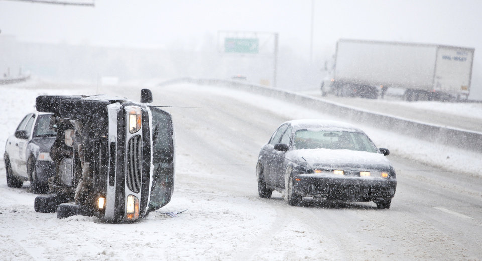 Photo - Motorist drive around a overturned SUV on the Broadway Extension near I-44 in Oklahoma City, Oklahoma January 29, 2010. Photo by Steve Gooch, The Oklahoman