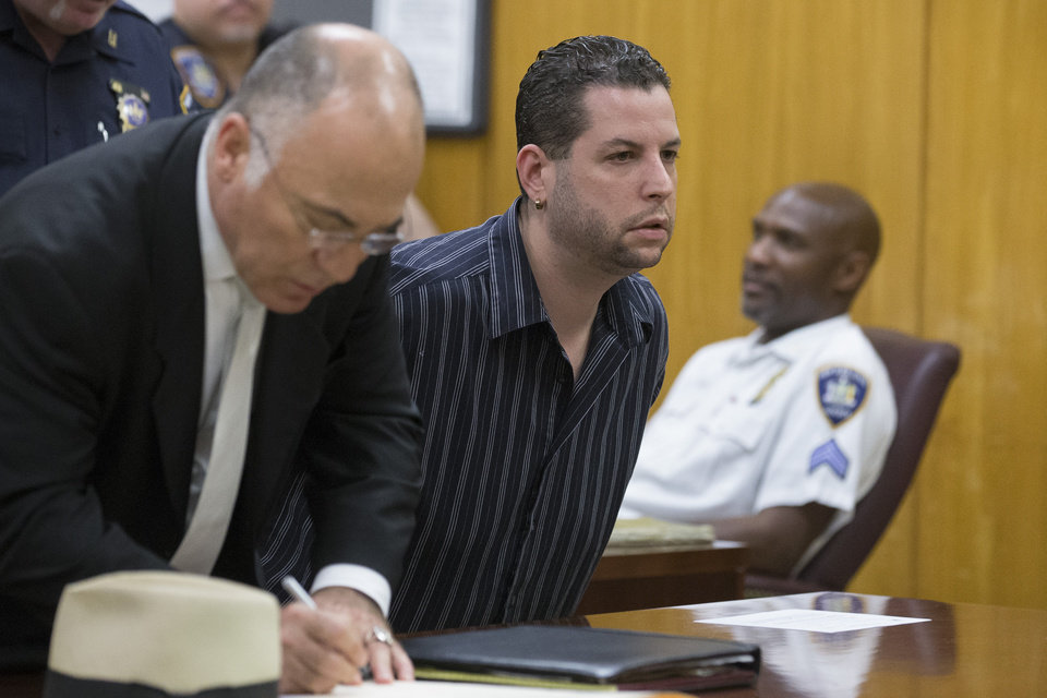 Photo - Brandon Taylor, center, attends his arraignment at Manhattan Supreme Court, Wednesday, July 2, 2014, in New York. Manhattan District Attorney Cyrus R. Vance Jr. and city Department of Investigation Commissioner Mark Peters announced earlier that morning the indictment of several individuals and businesses on charges including grand larceny, fraud, forgery, and evidence tampering through a building site safety inspection scam. (AP Photo/John Minchillo)