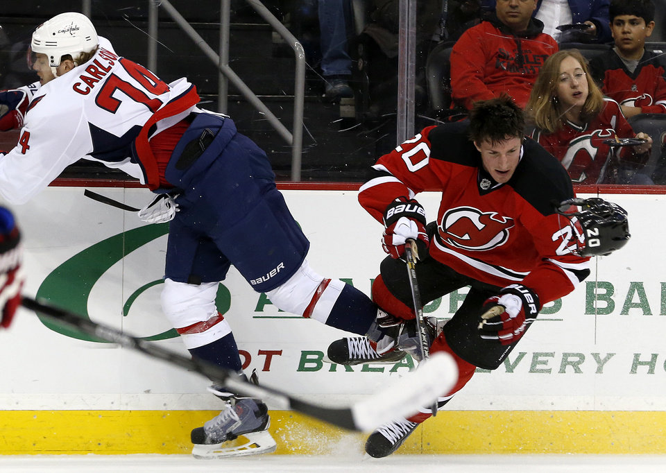 Photo - New Jersey Devils center Ryan Carter (20) loses his helmet after colliding with Washington Capitals defenseman John Carlson (74) during the first period of an NHL hockey game, Friday, April 4, 2014, in Newark, N.J. (AP Photo/Julio Cortez)