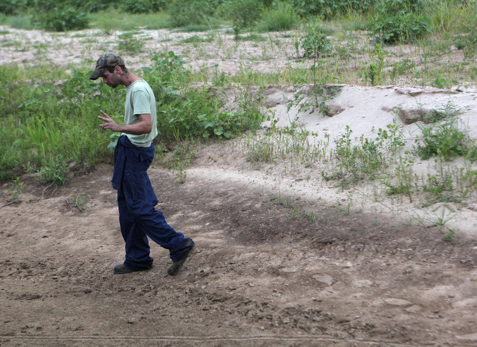 Johnny Heskett looks for hog tracks during a hunting trip near Indianola, Okla., Saturday, July 7, 2012.  Photo by Garett Fisbeck, The Oklahoman
