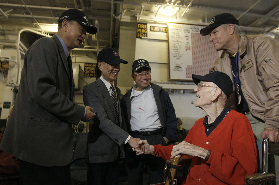 Photo -   Major Thomas Griffin, seated at right, shakes hands with Lt. Col. Chu Chen as he enters the USS Hornet before a news conference to commemorate the 70th Anniversary of the Tokyo attack by the Doolittle Raiders in Alameda, Calif., Saturday, May 5, 2012. Also pictured at left is John Fu. Survivors of a daring World War II aerial bombing of Japan are gathering in Alameda on the 70th anniversary of the attack. The