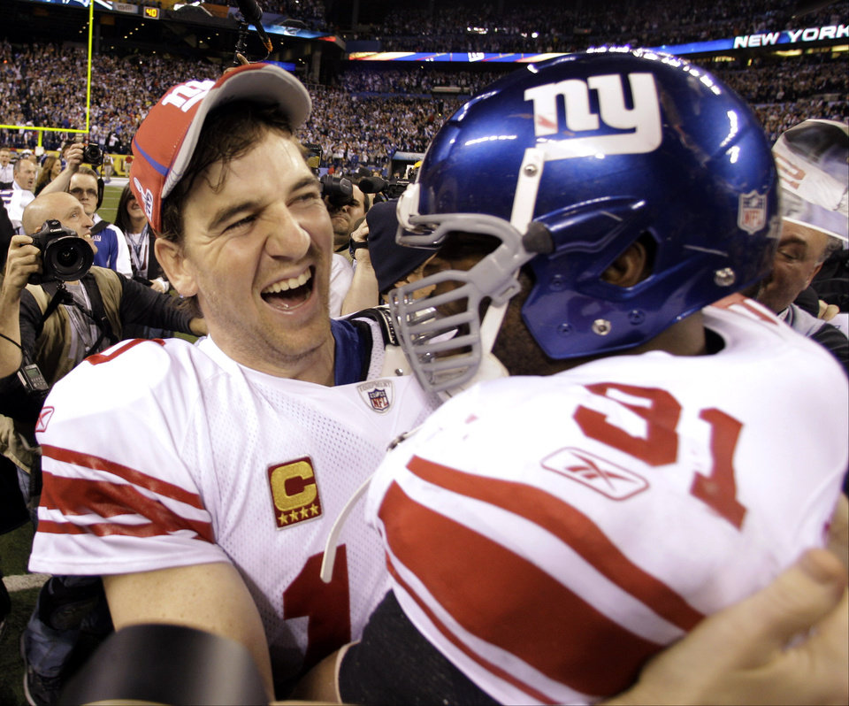 New York Giants quarterback Eli Manning, left, and Aaron Ross celebrate their team\'s 21-17 win over the New England Patriots in the NFL Super Bowl XLVI football game, Sunday, Feb. 5, 2012, in Indianapolis. (AP Photo/Eric Gay) ORG XMIT: SB528