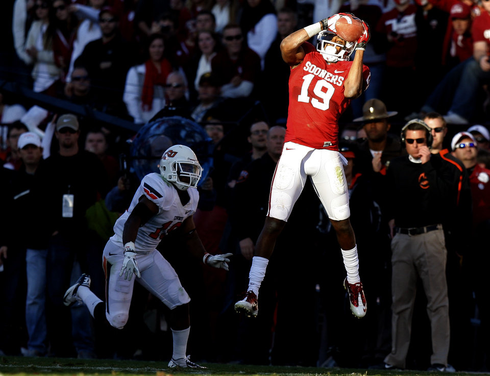 Photo - Oklahoma's Justin Brown (19) catches a pass in front of Oklahoma State's Brodrick Brown (19) during the Bedlam college football game between the University of Oklahoma Sooners (OU) and the Oklahoma State University Cowboys (OSU) at Gaylord Family-Oklahoma Memorial Stadium in Norman, Okla., Saturday, Nov. 24, 2012. Oklahoma won 51-48. Photo by Bryan Terry, The Oklahoman