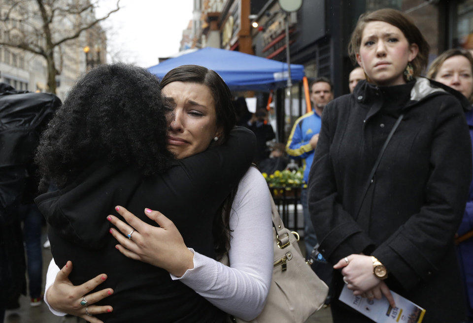 Photo - Olivia Savarino, center, hugs Christelle Pierre-Louis, left, as Callie Benjamin, right, looks on near the finish line of the Boston Marathon during ceremonies on Boylston Street, Tuesday, April 15, 2014, in Boston. Savarino and Benjamin were working at the Forum restaurant when a bomb went off in front of the building on April 15, 2013. (AP Photo/Steven Senne)