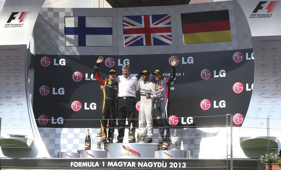 Photo - From left, second place Lotus driver Kimi Raikkonen of Finland, Mercedes team prinipal Ross Brawn, Mercedes driver Lewis Hamilton of Britain, winner, and third place Red Bull driver Sebastian Vettel of Germany stand on the podium after the Hungarian Formula One race at the Hungaroring racetrack, near Budapest, Hungary, Sunday, July 28, 2013. (AP Photo/Luca Bruno)