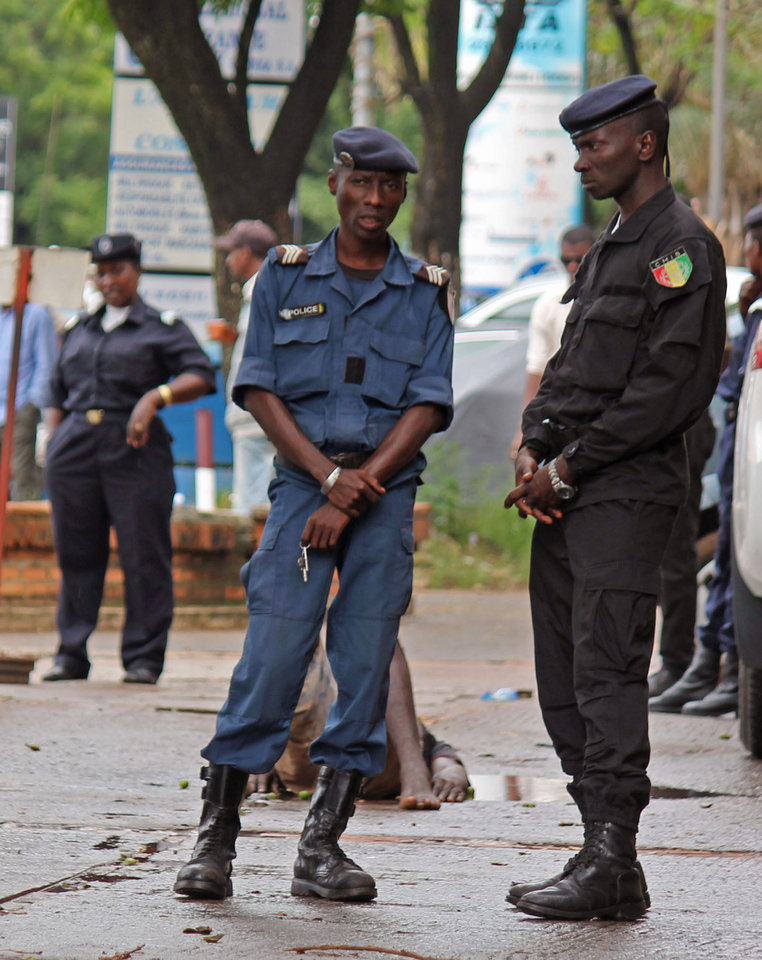 Photo - Guinea Police secure the area in front of a man who collapsed in a puddle of water on the street, and people would not approach him as they fear he may be suffering from the Ebola virus in the city of Conakry, Guinea, Wednesday, Aug. 6, 2014. The man lay in the street for several hours before being taken to an Ebola control centre for assessment.  The World Health Organization has began an emergency meeting on the Ebola crisis, and said at least 932 deaths in four countries are blamed on the virus, with many hundreds more being treated in quarantine conditions. (AP Photo/ Youssouf Bah)