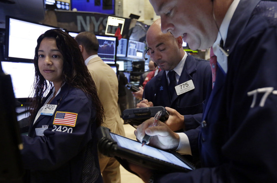 Photo - Specialist Wingszi Chiang, left, works at her post on the floor of the New York Stock Exchange Wednesday, Aug. 6, 2014. U.S. stocks are little changed in early trading Wednesday as investors worry about escalating tensions between Russia and the Ukraine. Investors were also holding back after two larger merger bids were pulled. (AP Photo/Richard Drew)