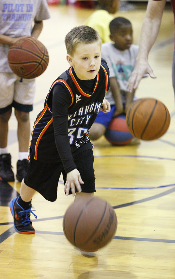 Photo - Wyatt Geissler, 6, goes through a drill during March Madness basketball camp at the YMCA in Bethany.