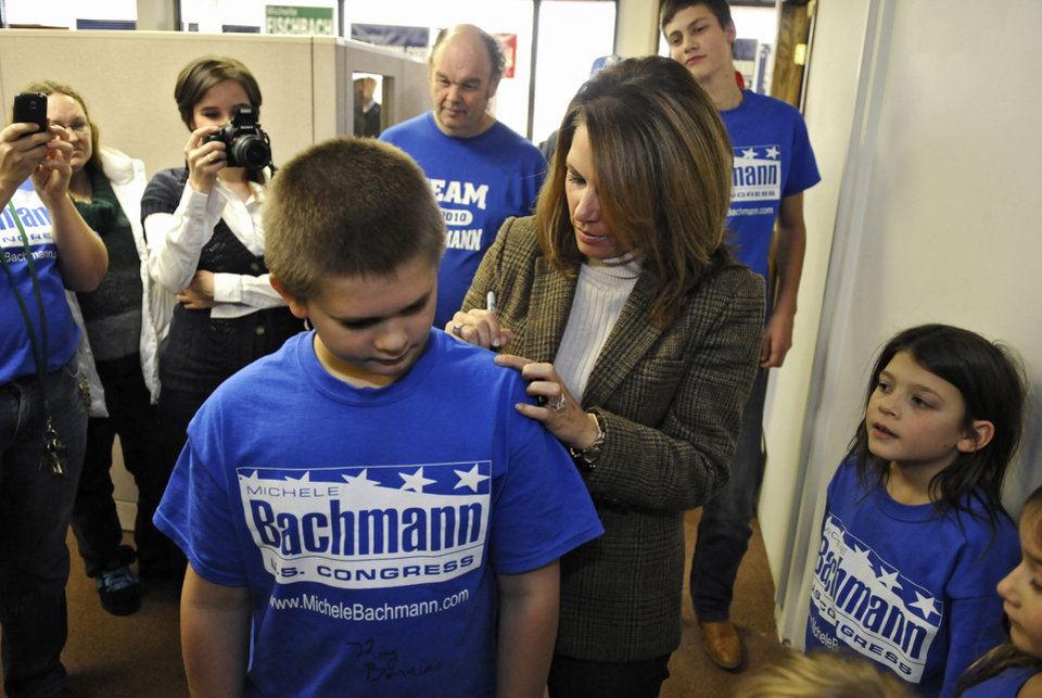 Photo -   U.S. Rep. Michele Bachmann signs supporter's T-shirts during a visit to her St. Cloud, Minn., campaign headquarters Saturday, Nov. 3, 2012. (AP Photos/The St. Cloud Times, Dave Schwarz) NO SALES
