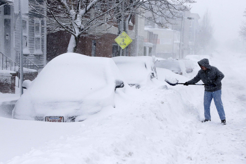 A man shovels out a car on Third street in the South Boston neighborhood of Boston, Saturday, Feb. 9, 2013. A behemoth storm packing hurricane-force wind gusts and blizzard conditions swept through the Northeast on Saturday, dumping more than 2 feet of snow on New England and knocking out power to 650,000 homes and businesses. (AP Photo/Gene J. Puskar)