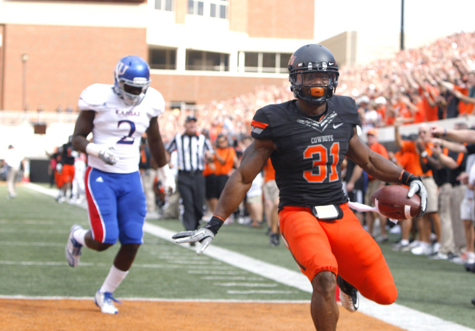 Photo - Oklahoma State's Jeremy Smith (31) celebrates a touchdown in front of Kansas' Darius Willis (2) during the first half of the college football game between the Oklahoma State University Cowboys (OSU) and the University of Kansas Jayhawks (KU) at Boone Pickens Stadium in Stillwater, Okla., Saturday, Oct. 8, 2011. Photo by Sarah Phipps, The Oklahoman