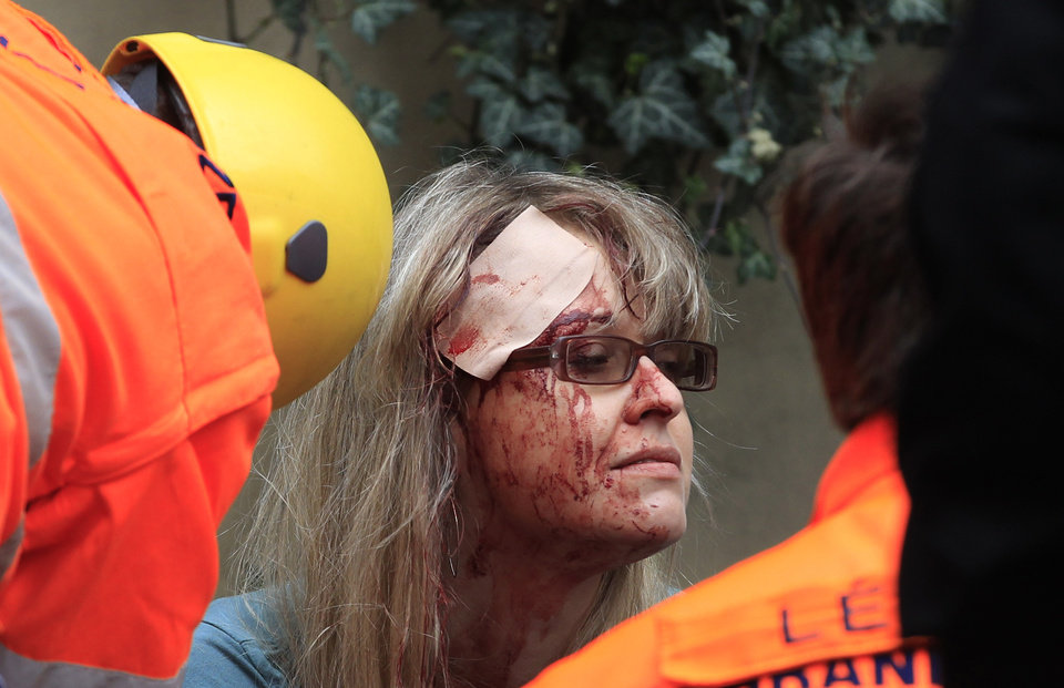 Photo - Paramedics help an injured woman after an explosion in downtown Prague, Czech Republic, Monday, April 29, 2013. Police said a powerful explosion has damaged a building in the center of the Czech capital and they believe some people are buried in the rubble. (AP Photo/Petr David Josek)
