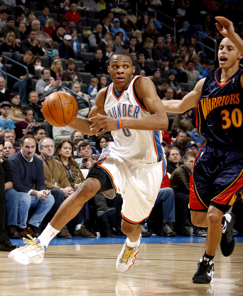 Photo - Oklahoma City's Russell Westbrook (0) drives to the basket as Golden State's Stephen Curry (30) defends during the NBA game between the Oklahoma City Thunder and Golden State Warriors, Sunday, Jan. 31, 2010, at the Ford Center in Oklahoma City. Photo by Sarah Phipps, The Oklahoman