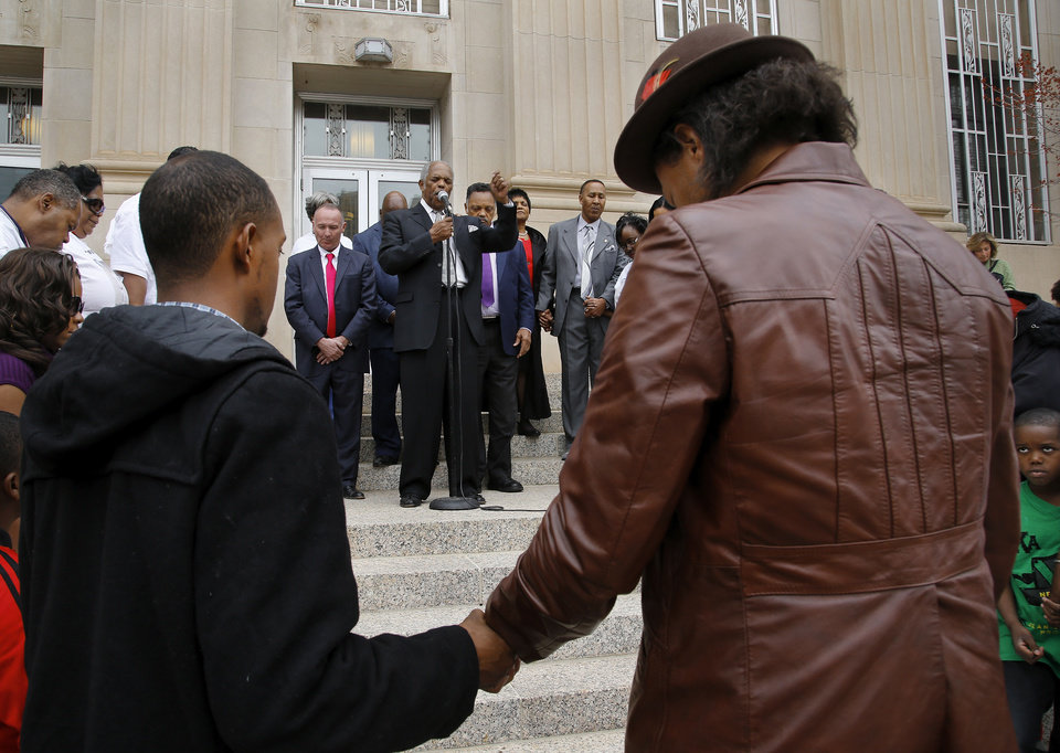 Photo - A prayer led by the Rev. John A. Reed Jr., senior pastor of Fairview  Missionary Baptist Church, concludes a rally in which the Rev. Jesse Jackson joined local pastors and civil rights leaders in a march  downtown.  Photo by Jim Beckel, The Oklahoman