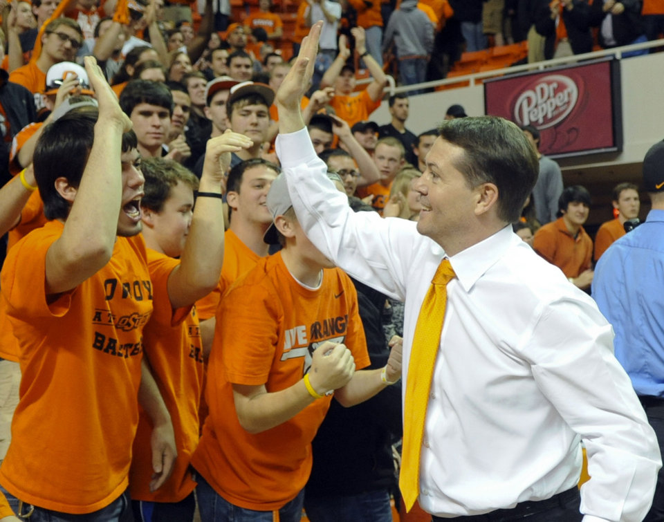 Oklahoma State head coach Travis Ford, right, celebrates with fans following an NCAA college basketball game against Baylor in Stillwater, Okla., Wednesday, Feb. 06, 2012. Oklahoma State defeated Baylor 69-67. (AP Photo/Brody Schmidt)
