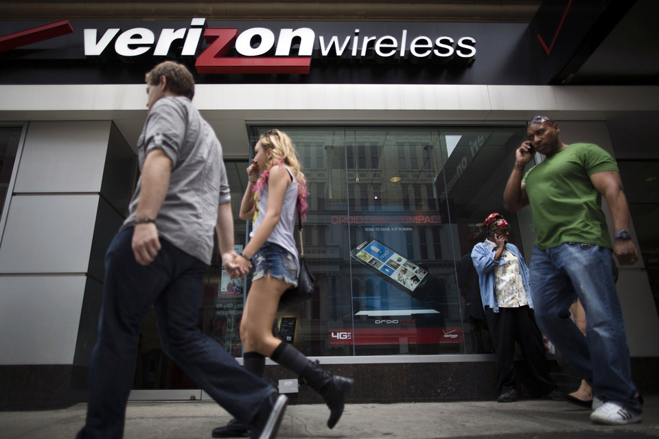 Photo - Pedestrians pass a Verizon Wireless store on Canal Street, Thursday, June 6, 2013, in New York. The Obama administration on Thursday, June 6, 2013, defended the government's need to collect telephone records of American citizens, calling such information