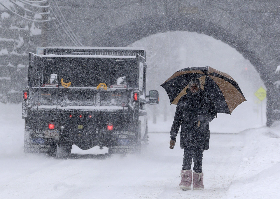 Photo - Trishia Williams, of Norwood, Mass., uses an umbrella while making her way to work on a snowy road in Norwood, Wednesday, Feb. 5, 2014.  Six to 12 inches of snow is expected around Boston, with 3 to 6 inches in southeastern areas before changing to sleet and rain Wednesday. (AP Photo/Steven Senne)