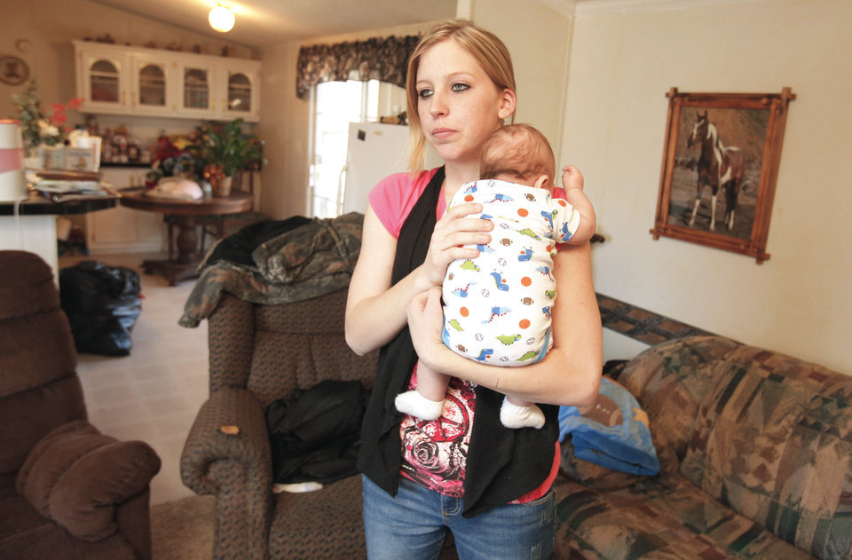 Sarah McKinley, 18, holds her son, Justin, on Wednesday in the living room of her mobile home in Blanchard. She fatally shot an intruder in her home on New Year�s Eve.Photo by Steve Sisney, The Oklahoman