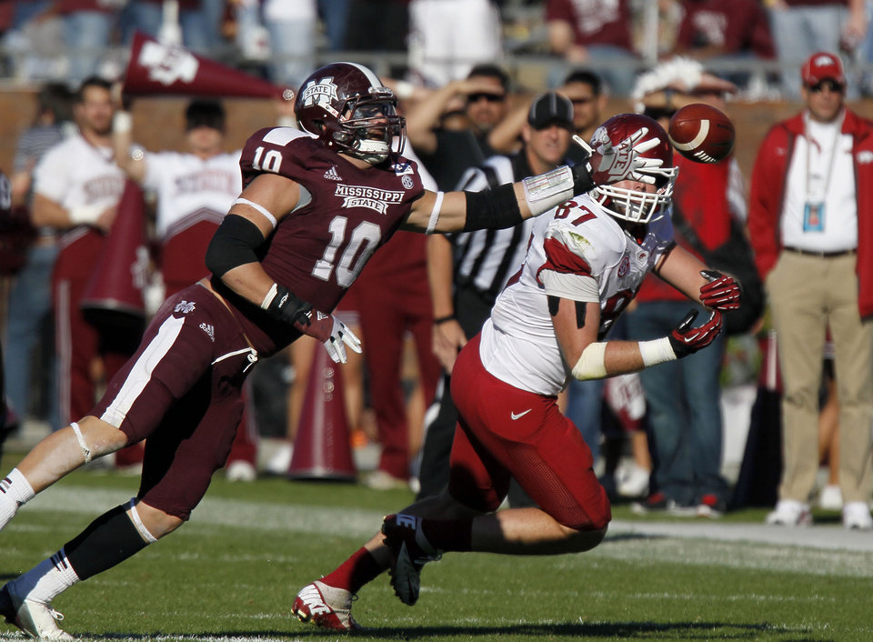 Photo -   Mississippi State linebacker Cameron Lawrence (10) knocks away a pass intended for Arkansas tight end Austin Tate (87) in the third quarter of an NCAA college football game in Starkville, Miss., Saturday, Nov. 17, 2012. Mississippi State won 45-14. (AP Photo/Rogelio V. Solis)