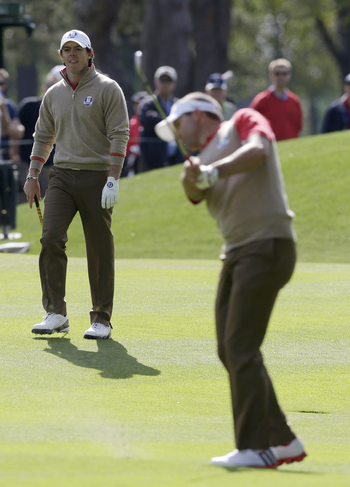 Photo -   Europe's Rory McIlroy, left, watches Sergio Garcia take a shot on the 11th hole during a practice round at the Ryder Cup PGA golf tournament Thursday, Sept. 27, 2012, at the Medinah Country Club in Medinah, Ill. (AP Photo/Chris Carlson)