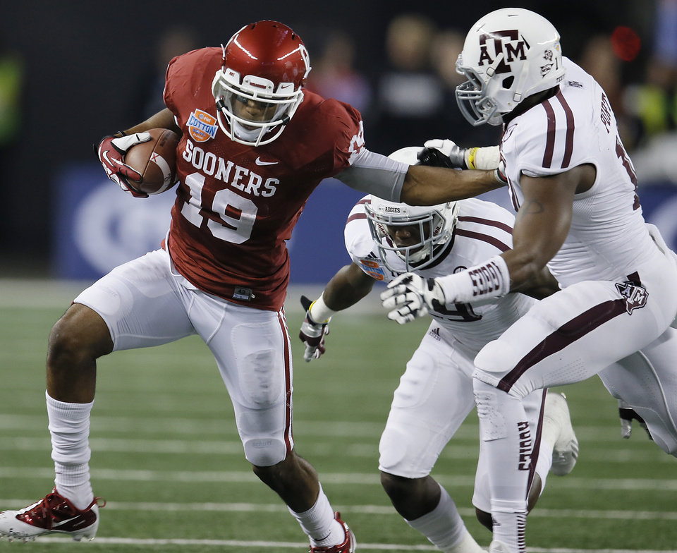 Photo - Oklahoma's Justin Brown (19) stiff arms Texas A&M's Sean Porter (10) during the college football Cotton Bowl game between the University of Oklahoma Sooners (OU) and Texas A&M University Aggies (TXAM) at Cowboy's Stadium on Friday Jan. 4, 2013, in Arlington, Tx. Photo by Chris Landsberger, The Oklahoman