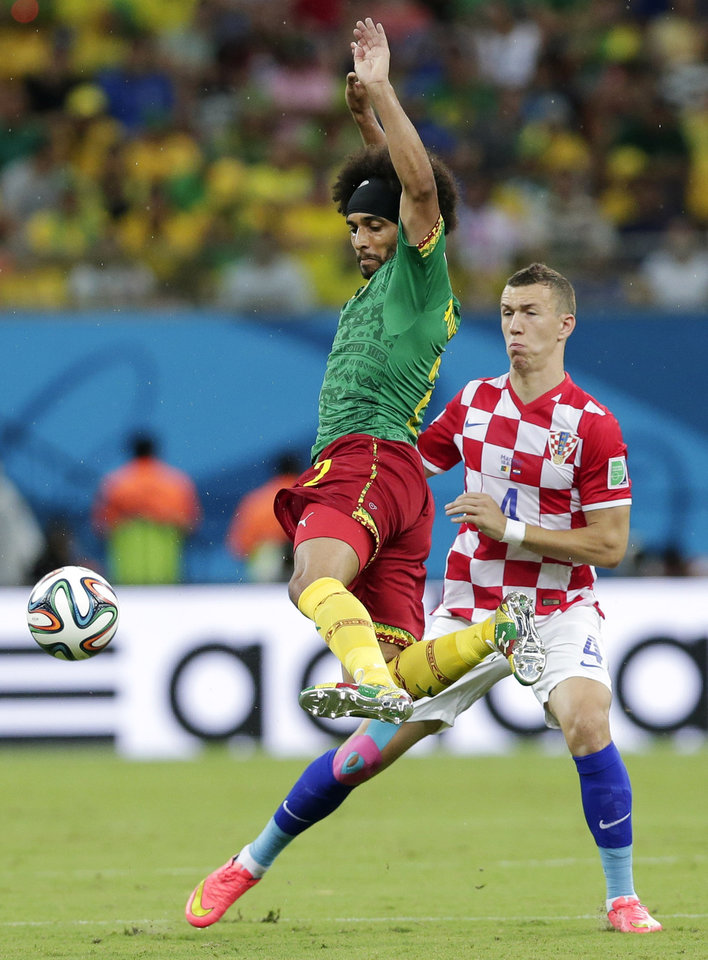 Photo - Cameroon's Benoit Assou-Ekotto, left, kicks the ball away from Croatia's Ivan Perisic during the group A World Cup soccer match between Cameroon and Croatia at the Arena da Amazonia in Manaus, Brazil, Wednesday, June 18, 2014.  (AP Photo/Marcio Jose Sanchez)
