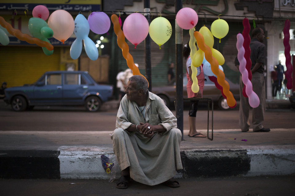 Photo - An Egyptian man waits for the morning prayer on a street decorated with balloons near the Sayyida Zeinab mosque on the first day of Eid al-Ahda in Cairo, Egypt, Tuesday, Oct. 15, 2013. Muslims worldwide are celebrating Eid al-Adha, or the Feast of the Sacrifice, by sacrificial killing of sheep, goats, cows or camels. The slaughter commemorates the biblical story of Abraham, who was on the verge of sacrificing his son to obey God's command, when God interceded by substituting a ram in the child's place. (AP Photo/Manu Brabo)