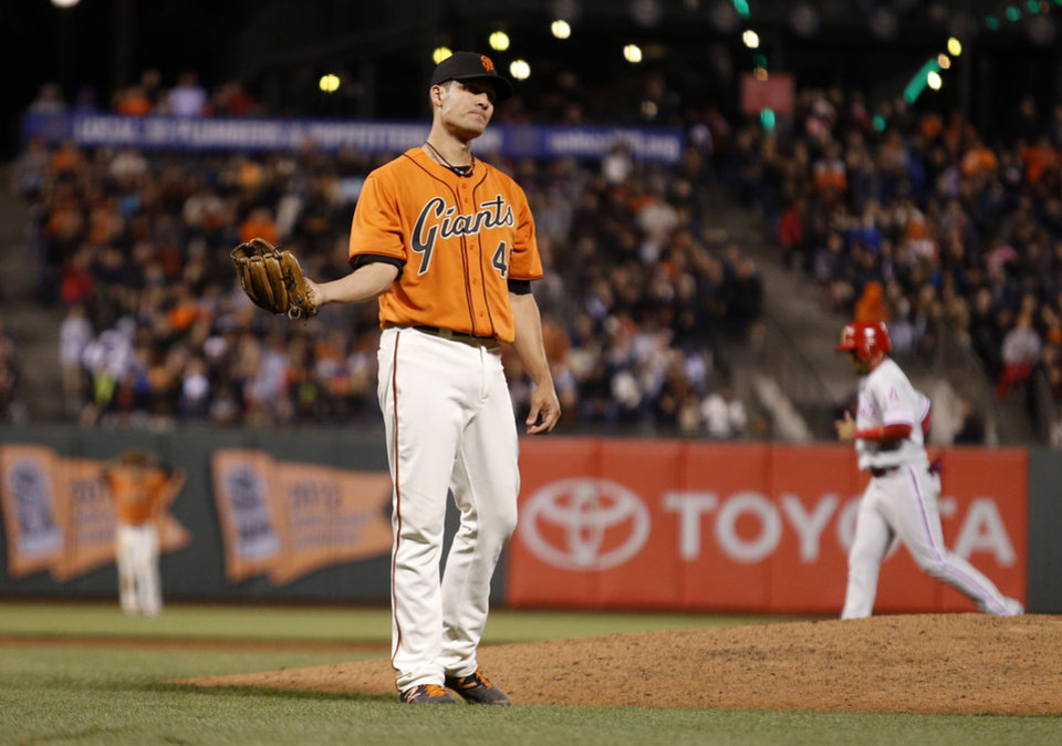 Photo - San Francisco Giants pitcher Javier Lopez reacts after hitting Philadelphia Phillies' Chase Utley with a pitch, forcing a run scored because the bases were loaded during the tenth inning of a baseball game, Friday, Aug. 15, 2014, in San Francisco. (AP Photo/Beck Diefenbach)