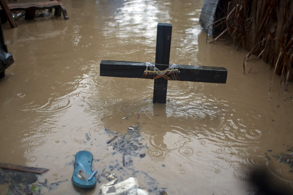 Photo -   A voodoo cross in honor of the Baron Samedi stands in floodwaters, triggered by Tropical Storm Isaac, at a place of worship in Port-au-Prince, Haiti, Saturday, Aug. 25, 2012. Tropical Storm Isaac swept across Haiti's southern peninsula early Saturday, dousing a capital city prone to flooding and adding to the misery of a poor nation still trying to recover from the 2010 earthquake. (AP Photo/Dieu Nalio Chery)