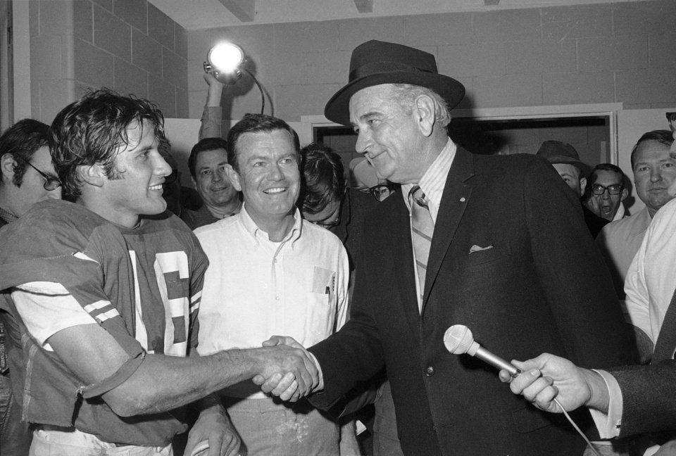 Photo - FILE - This Jan. 1, 1970 file photo shows former President Lyndon B. Johnson congratulating University of Texas quarterback James Street and coach Darrell Royal, center, in the dressing room after the Longhorns defeated Notre Dame in the Cotton Bowl in Dallas. The University of Texas says  Royal, who won two national championships and a share of a third, has died. He was 88. UT spokesman Nick Voinis on Wednesday, Nov. 7, 2012 confirmed Royal's death in Austin. Royal was close friends with former President Johnson, who attended Texas football games once his presidency ended.  (AP Photo/File)