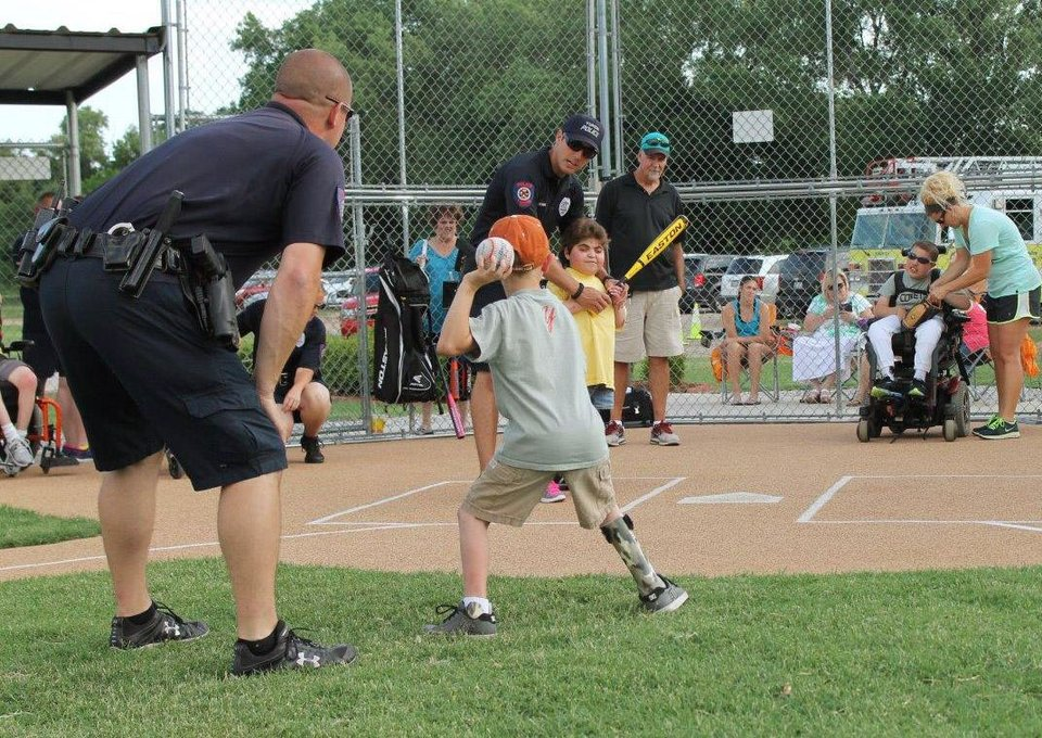 Photo -  Yukon police department members provide guidance as kids participate in the Yukon Spirit Baseball League. The league for special needs children has wrapped up its season. The league is sponsored by the Yukon police and fire departments and the parks and recreation department. PHOTO PROVIDED   PROVIDED